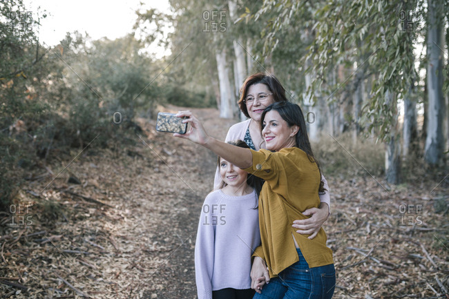 Grandmother daughter and girl taking a selfie in a forest with trees