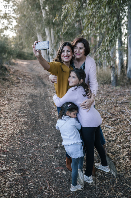 Three generations of women taking a selfie with their phone in a forest