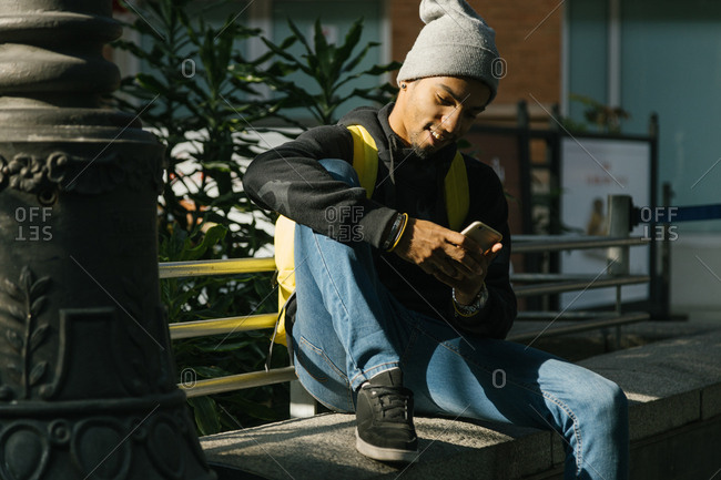 portrait of young hispanic man with hat sitting chatting
