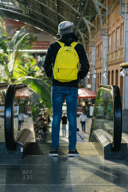 Hispanic young man with hat and yellow backpack on his back