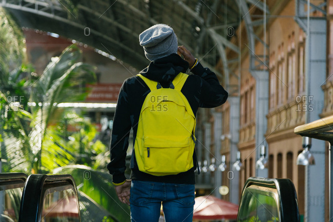 Hispanic young man with hat and yellow backpack talking with her smart phone on his back