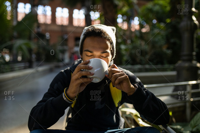 Hispanic young man with hat having a cup of coffee
