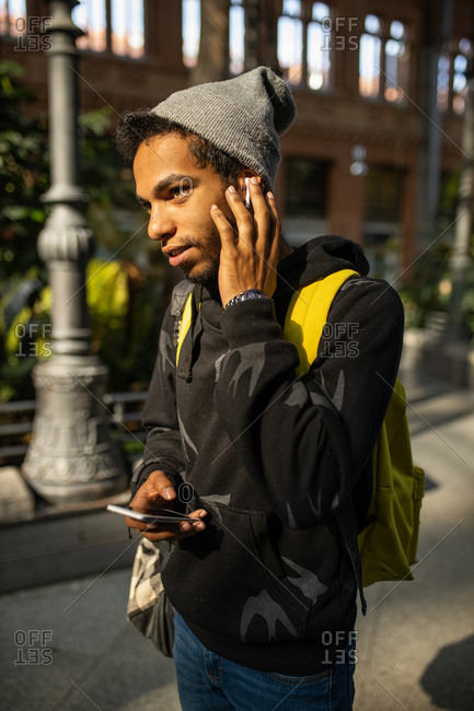 Hispanic young man with hat taking listening to music with his headphones