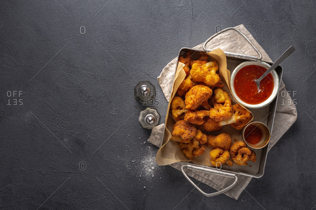 Cauliflower vegan buffalo wings with spicy sauce on dark background