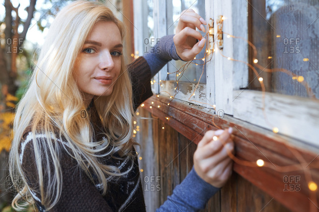 Woman hanging Christmas string light to the window of log cabin