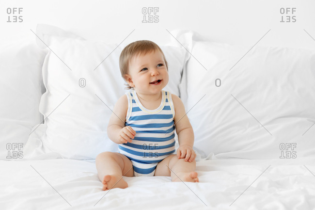 Smiling baby boy sitting on bed wearing striped onesie