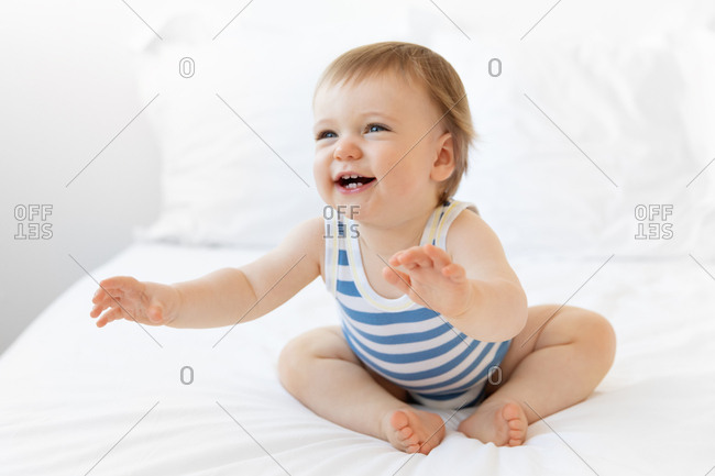 Laughing baby boy reaching out with arms extended