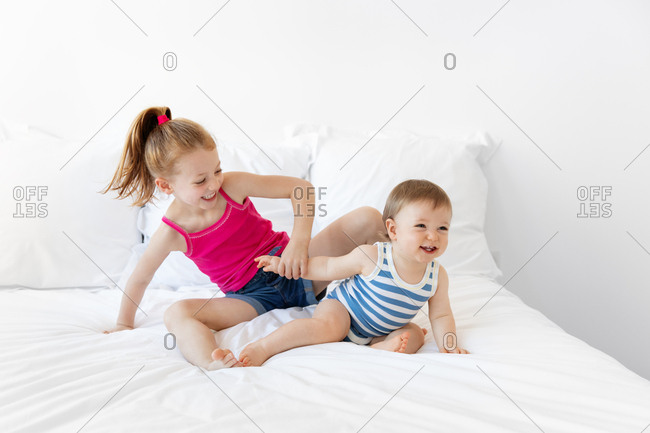 Baby boy and big sister playing on white bed