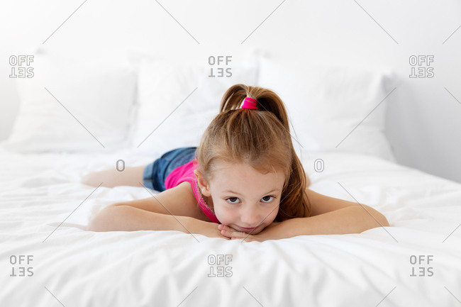 Young girl lying on bed with chin on hands
