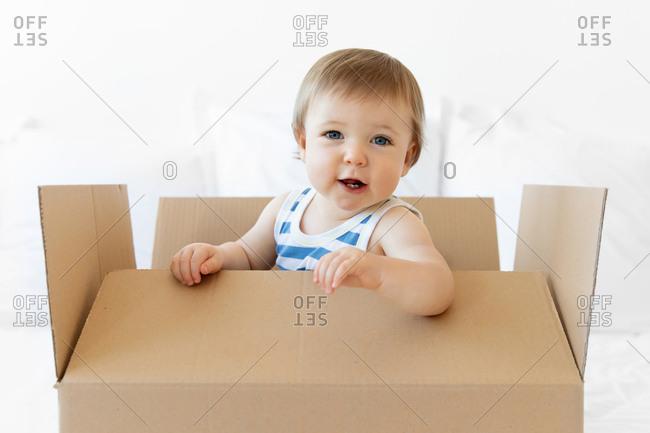 Blue-eyed baby sitting in cardboard box