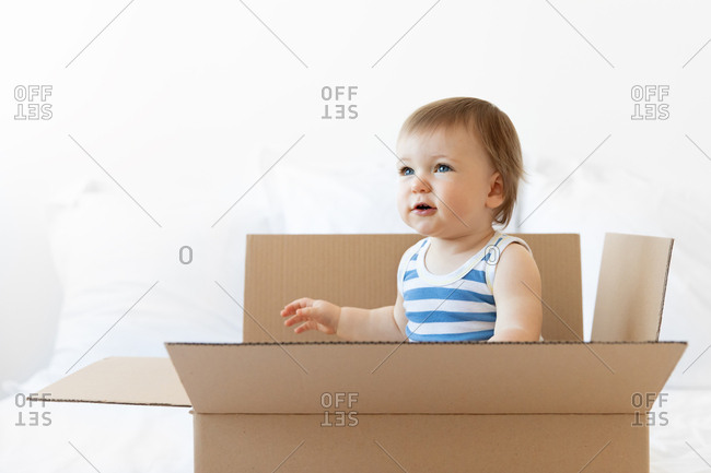 Cute baby boy sitting in delivery box