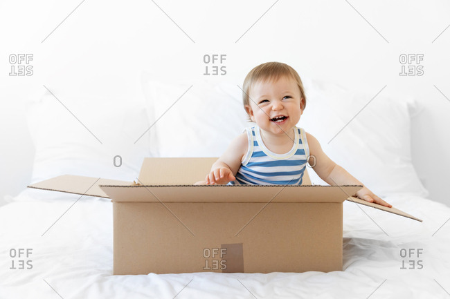 Cute laughing baby sitting in cardboard box