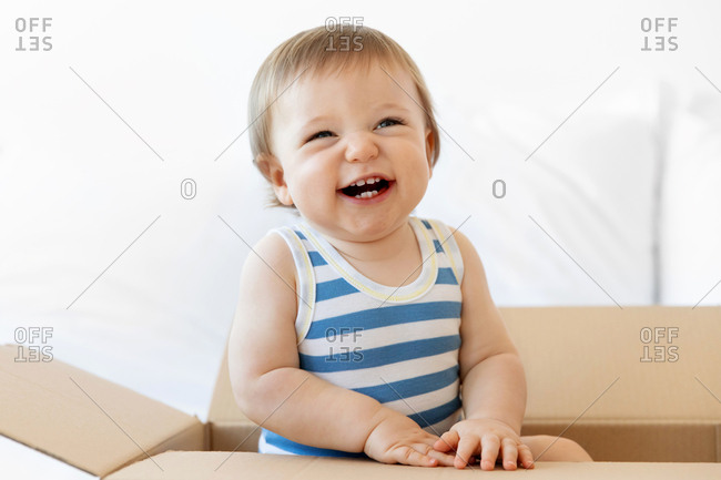 Laughing baby boy sitting in cardboard box