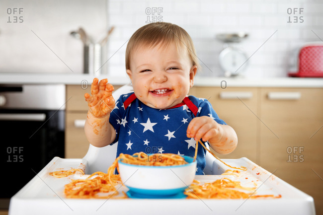 Happy baby making mess with spaghetti in high chair