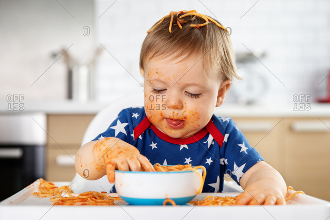 Funny baby boy eating spaghetti with his hands