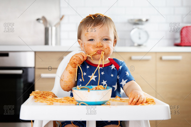 Funny baby eating spaghetti with his hands