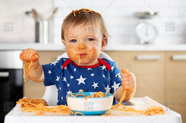 Funny toddler eating spaghetti with his hands