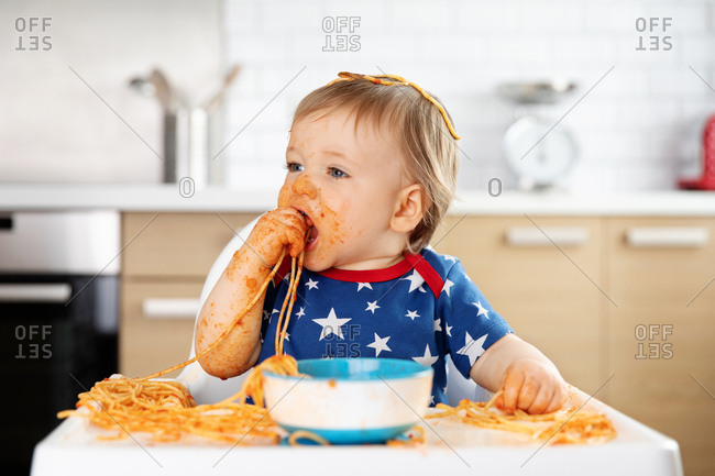 Messy baby eating spaghetti with his hands
