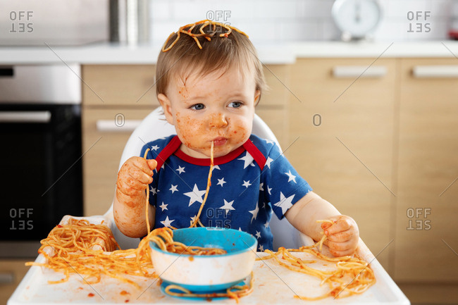 Messy baby with spaghetti hanging from mouth