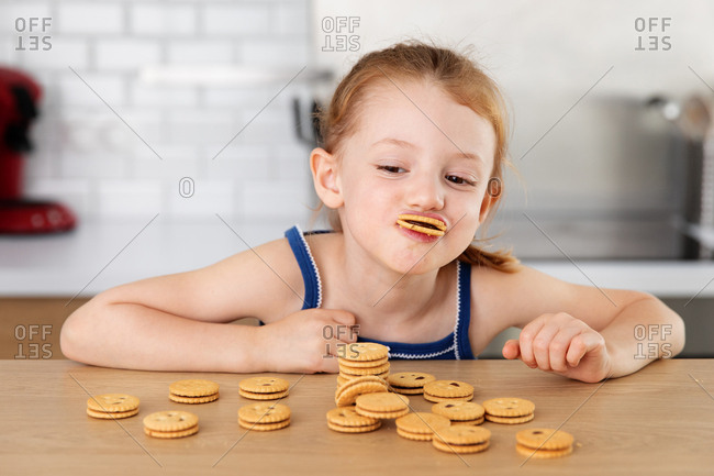 Funny little girl making goofy face with cookie