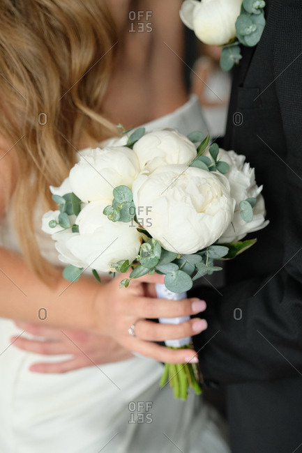 Close-up of a bride holding bouquet of white peonies and eucalyptus