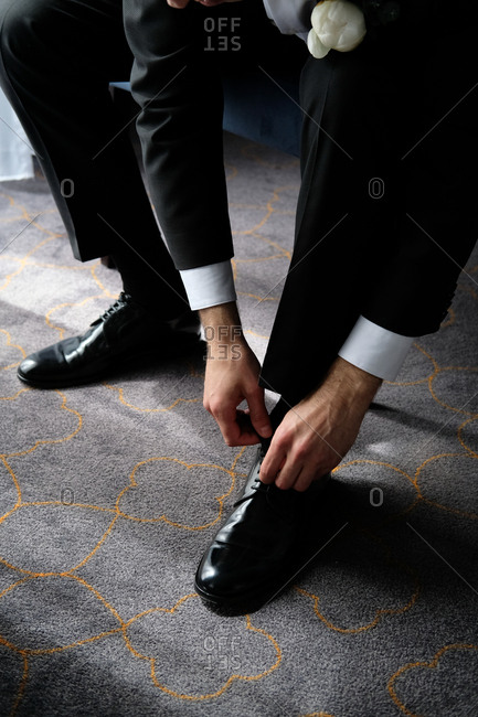 Groom tying his shoes before wedding ceremony