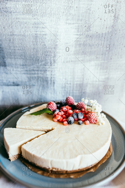 Fresh cheesecake with frozen berries with a blue background