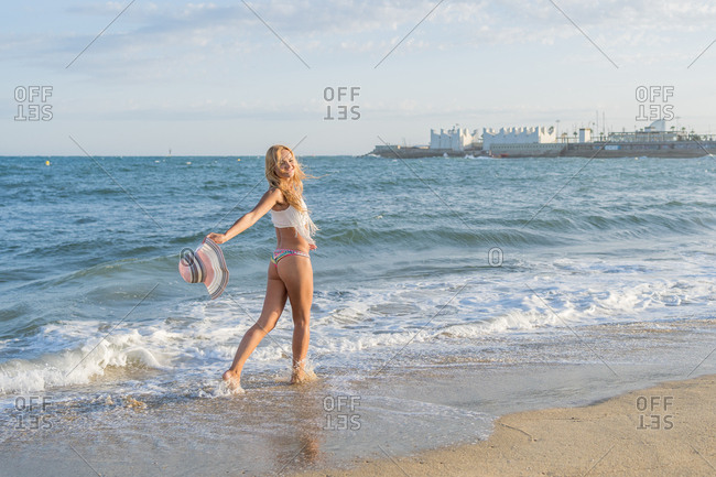 Russian woman smiling as she waves her hat on the shore of the beach