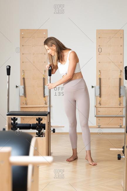 Beautiful sportswoman preparing equipment at reformer pilates studio.