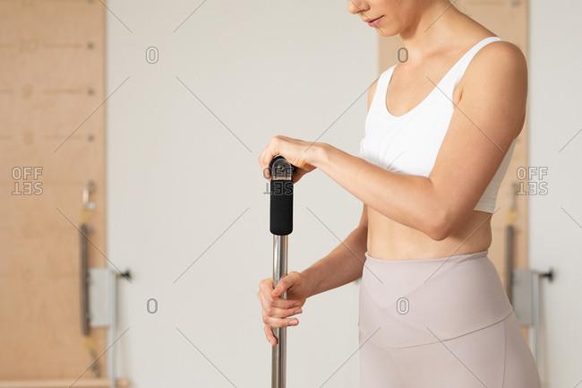 Unrecognizable sportswoman standing at pilates studio.
