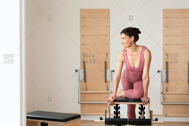 Portrait of beautiful smiling Caucasian sportswoman sitting on pilates chair.