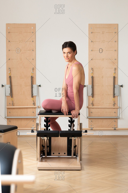 Portrait of beautiful smiling Caucasian sportswoman sitting on pilates chair and looking at the camera.