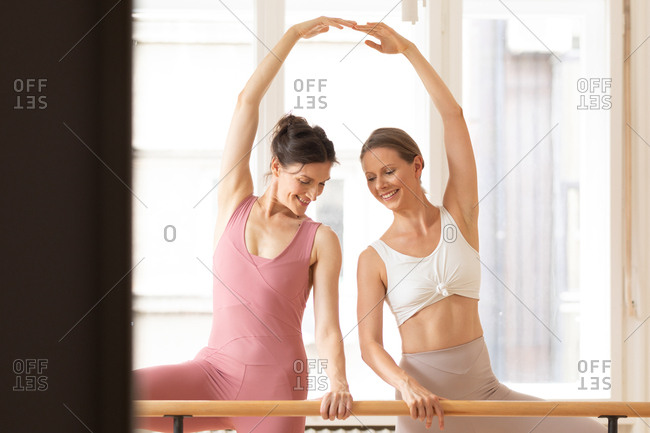 Two beautiful Caucasian women doing ballet training together using barre.