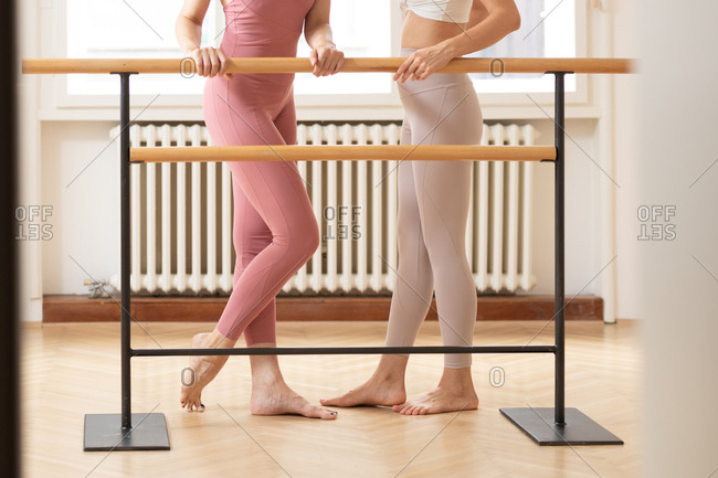 Legs of two ballet dancers standing together at ballet studio next to barre.