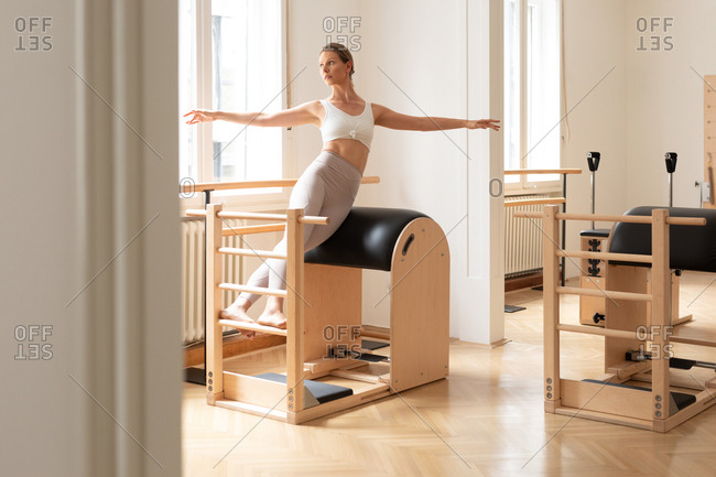 Beautiful Caucasian woman doing pilates exercise using equipment.