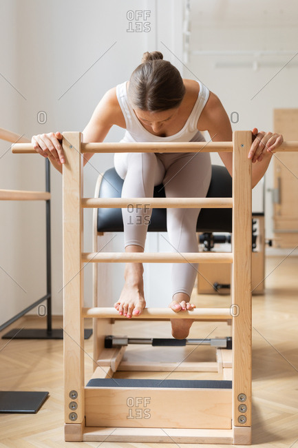 A woman doing pilates exercise using equipment.