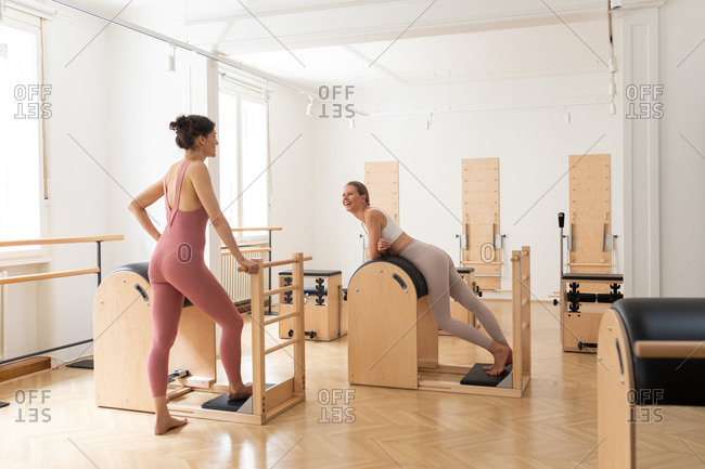 Two beautiful sportswomen chatting at pilates studio and looking happy.