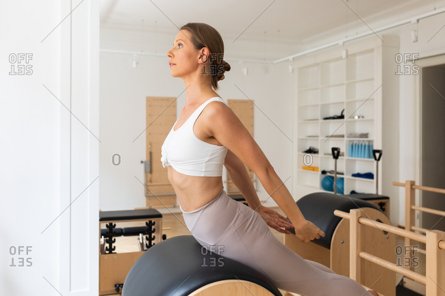 Pretty Caucasian woman doing pilates exercise at studio.