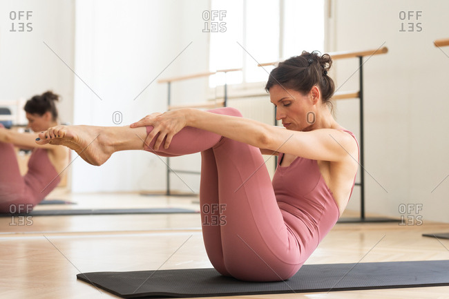 Beautiful woman in pink sporty overalls doing pilates exercise on mat.