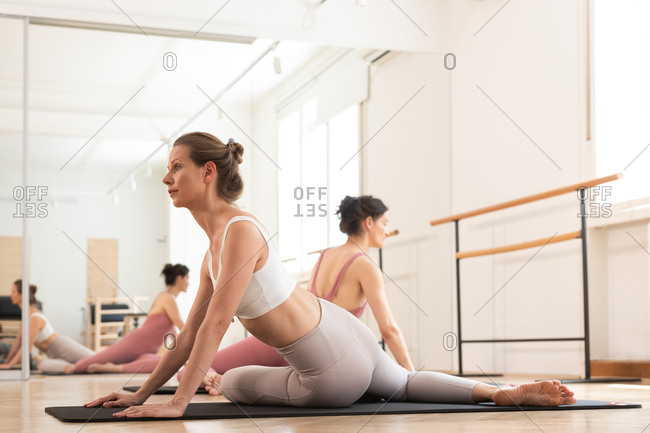 Two pretty women doing together exercise on mat at pilates studio.