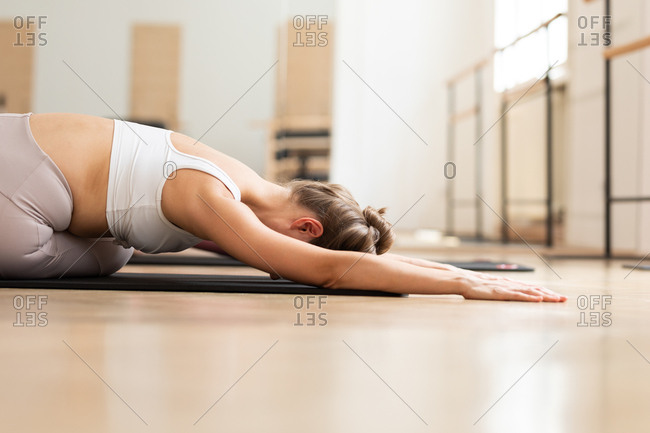 A woman doing yoga on mat.