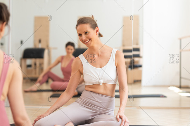 Pretty smiling woman sitting at pilates studio and smiling with instructor.
