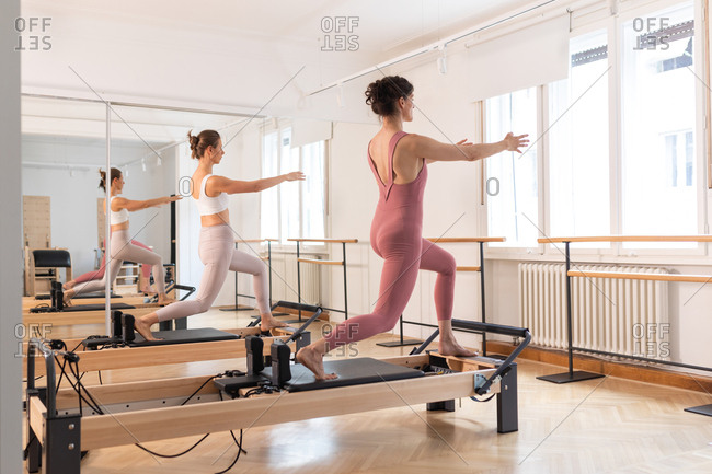 Two women doing reformer pilates exercise.