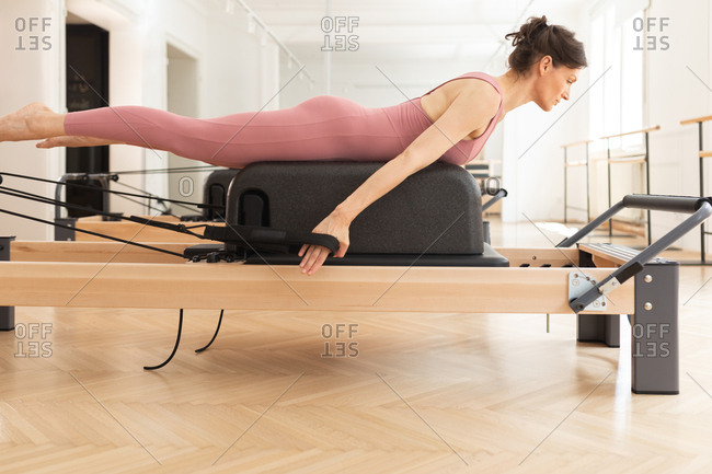 Pretty Caucasian woman doing reformer pilates exercise.