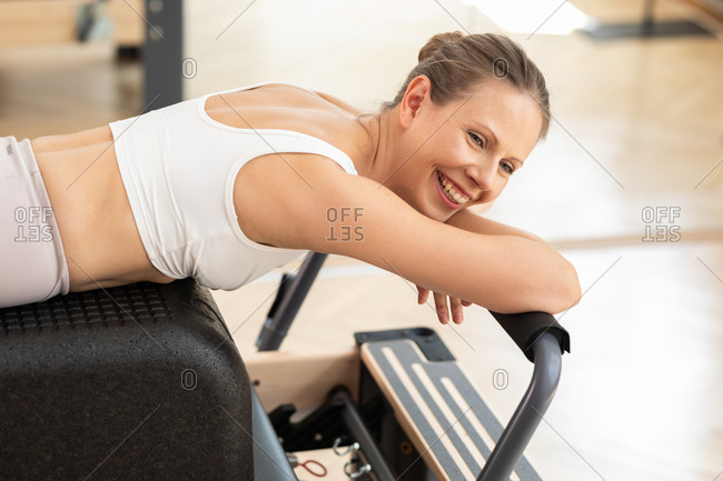 Pretty Caucasian smiling woman taking a break from reformer pilates training.