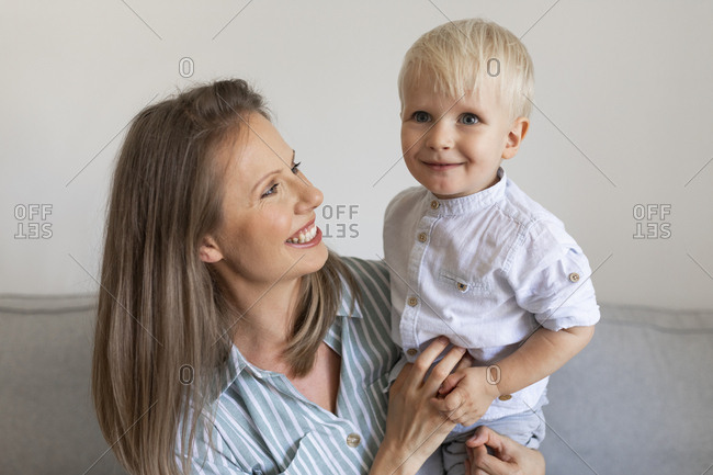 Portrait of mother smiling while holding her cute toddler son.