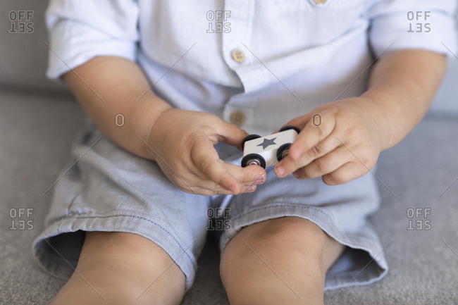 Hands of unrecognizable toddler  boy holding his car toy.