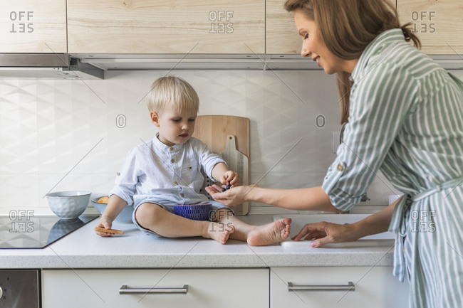 Mother giving blueberries to her cute little toddler son at the kitchen.