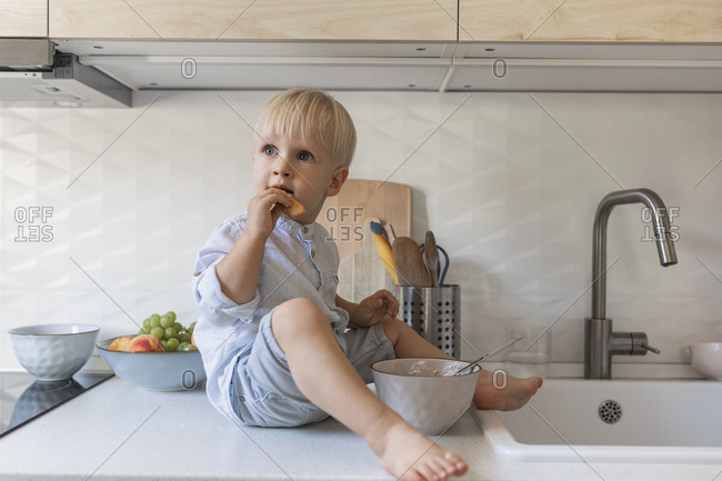 Cute blonde toddler boy sitting on the kitchen table.