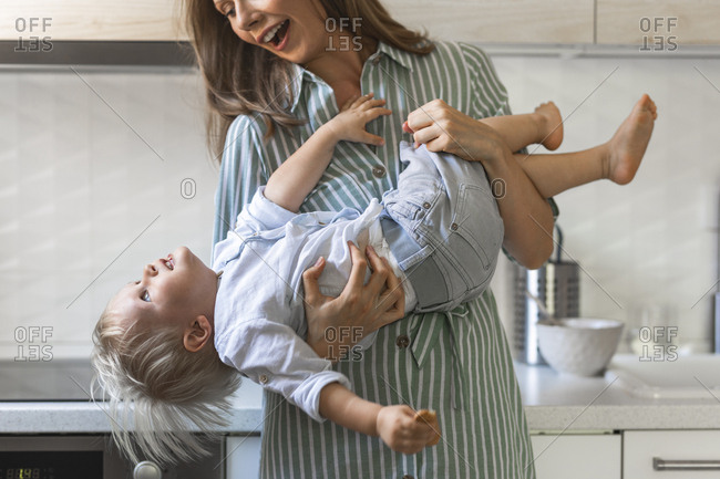 Happy mother holding her cute toddler son while standing at home.